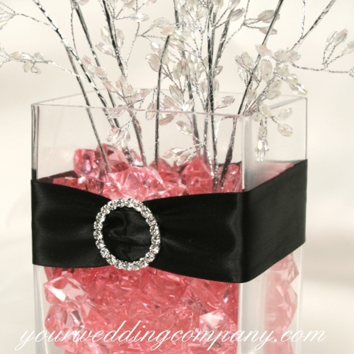 A reception centerpiece wrapped in black satin ribbon and accented ...