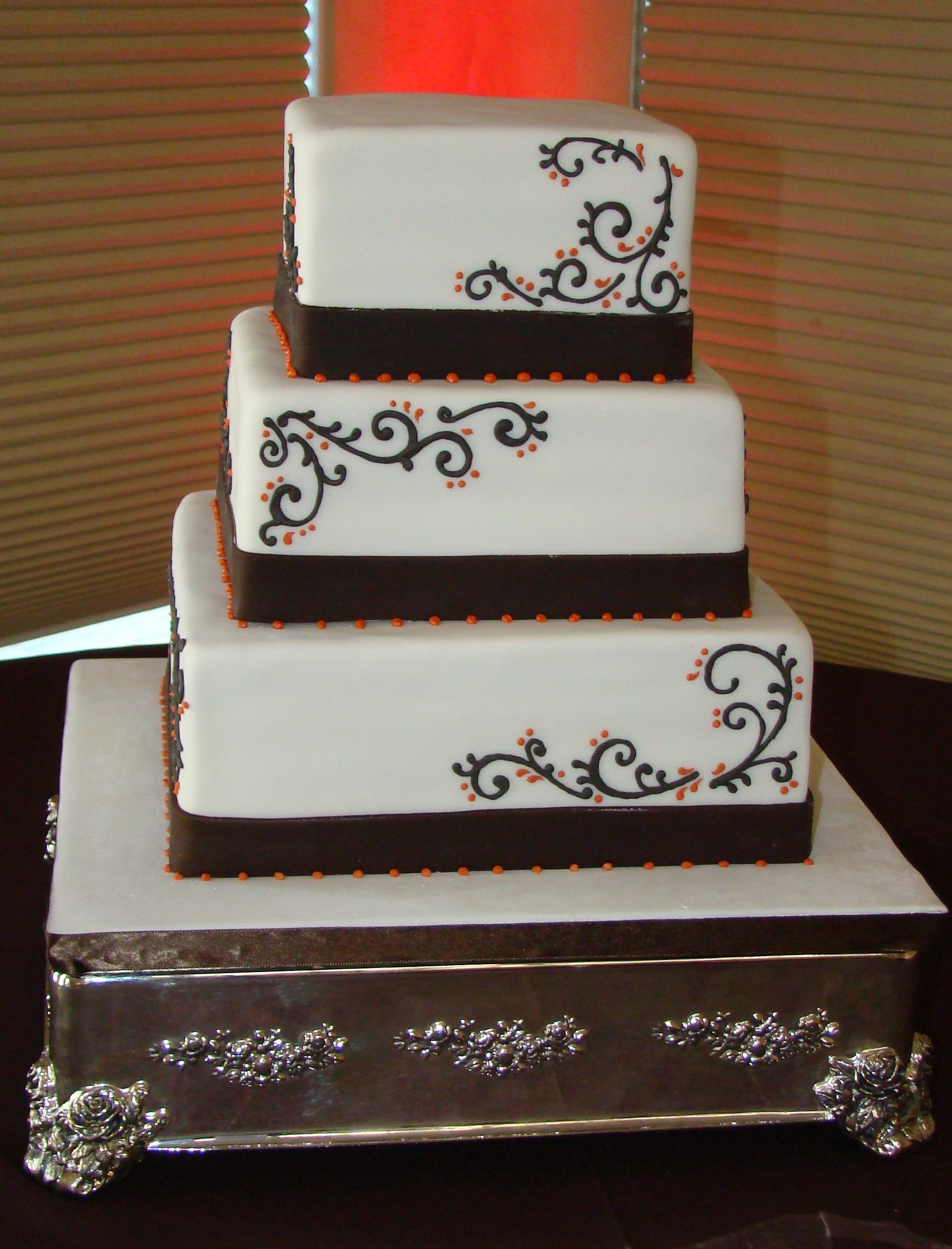 3 tier square cake with brown fondant ribbon and hand