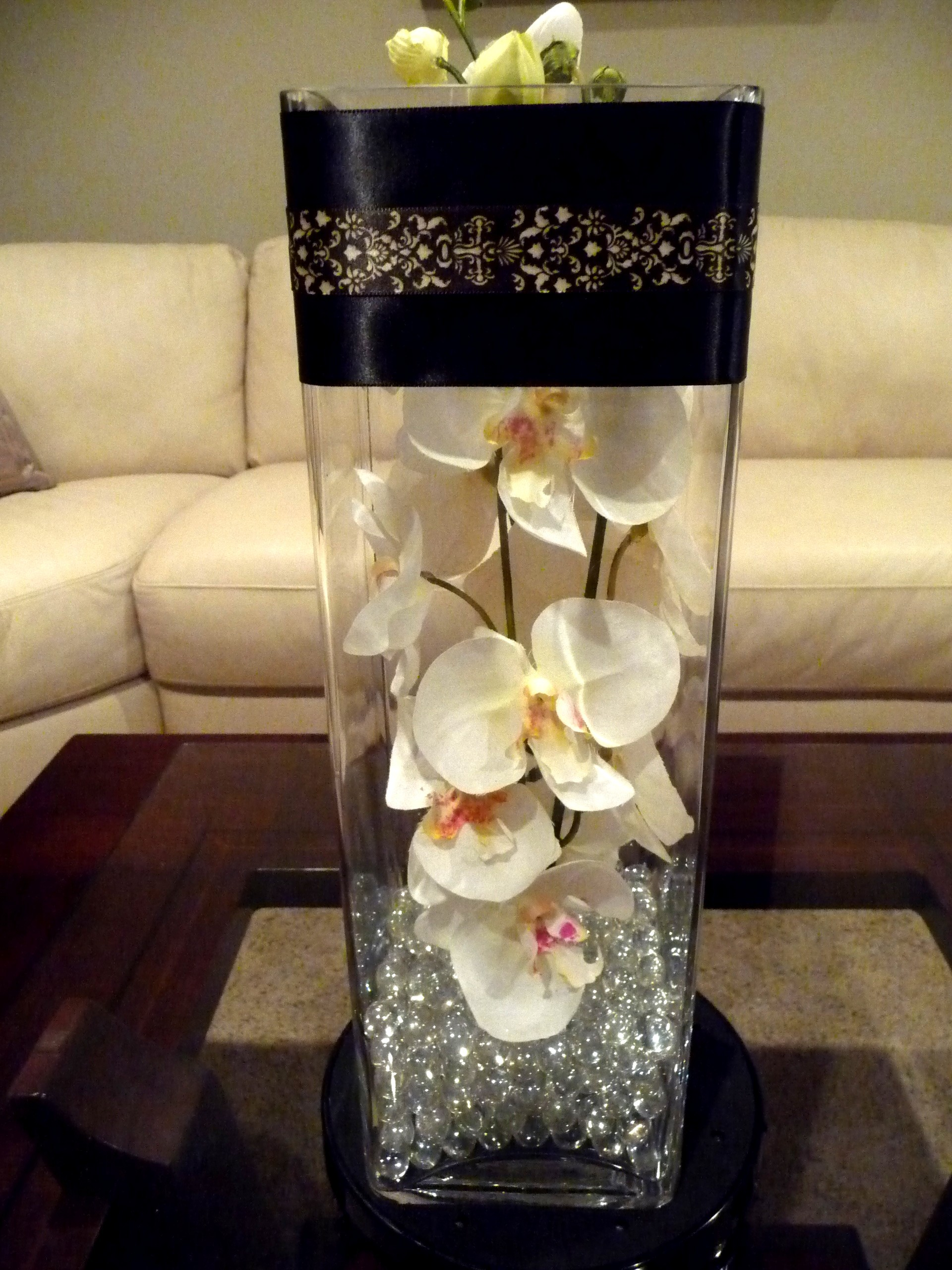 Tall square glass vase filled with acryllic beads and