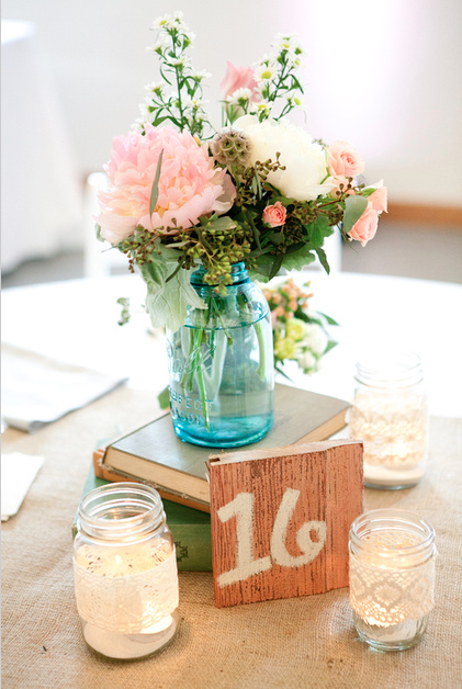 Centerpieces were placed on top of vintage books in mason for Angela florist decoration