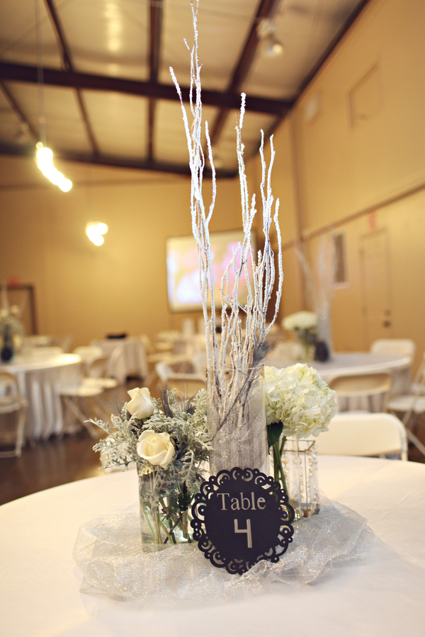 The reception table centerpieces featured tall white and