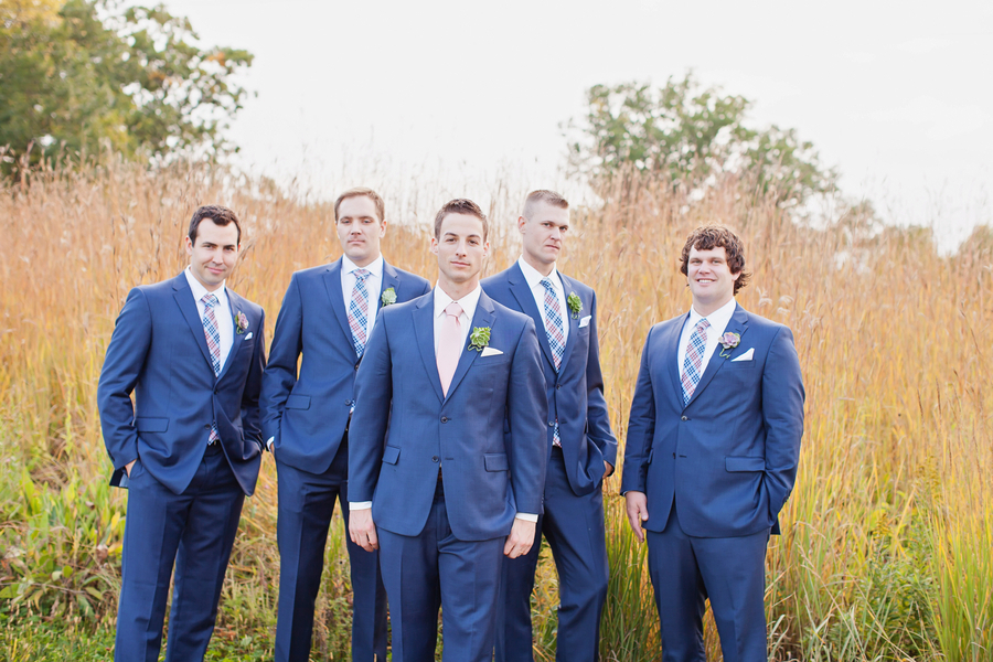 The handsome groomsmen wore navy suits paired with coral ...