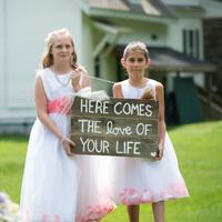 Flower Girls Carrying a Sign