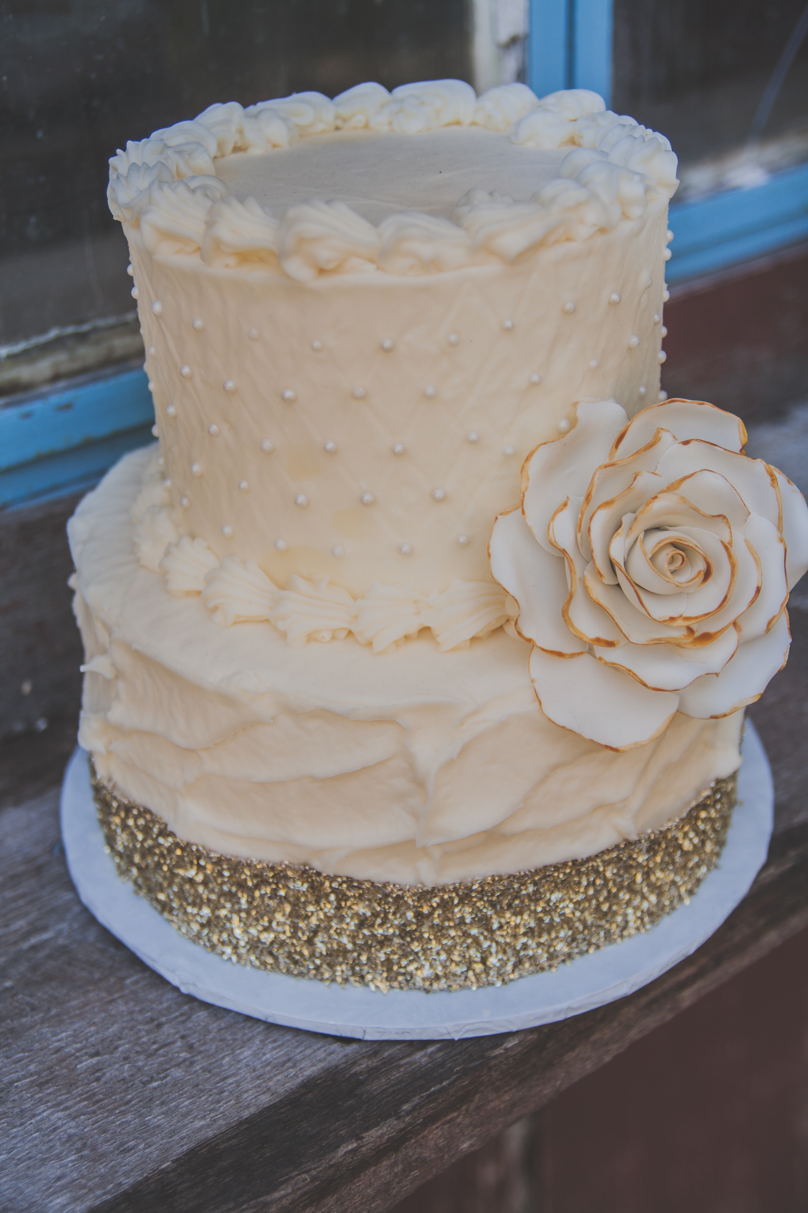 A twotier ivory buttercream cake decorated with sugar