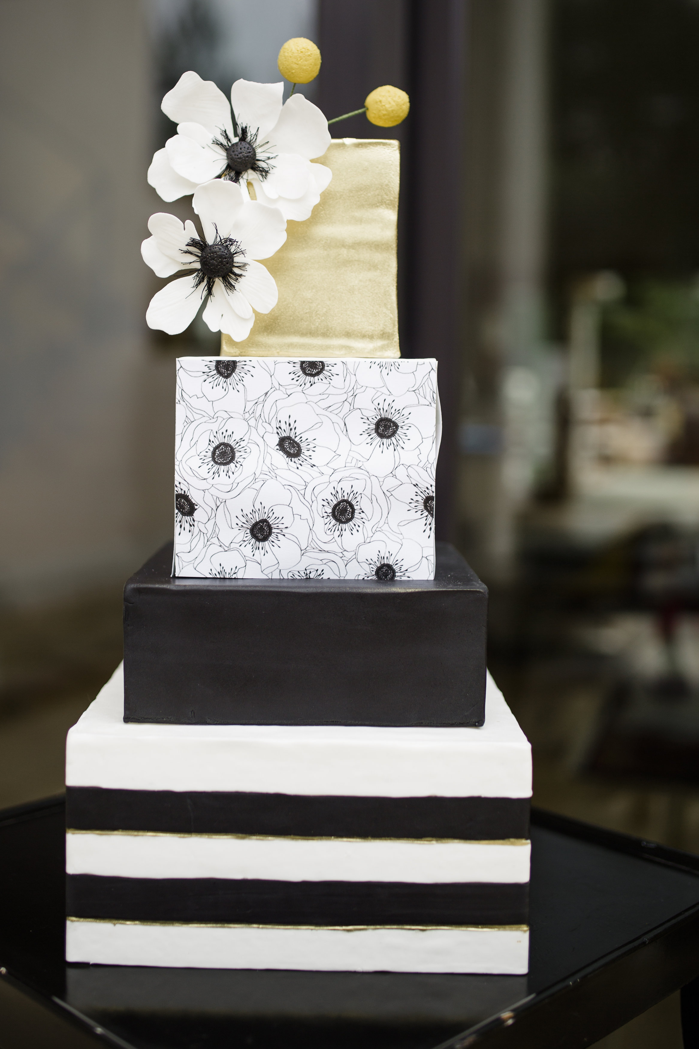 An amazing fourtier square cake featuring black and white