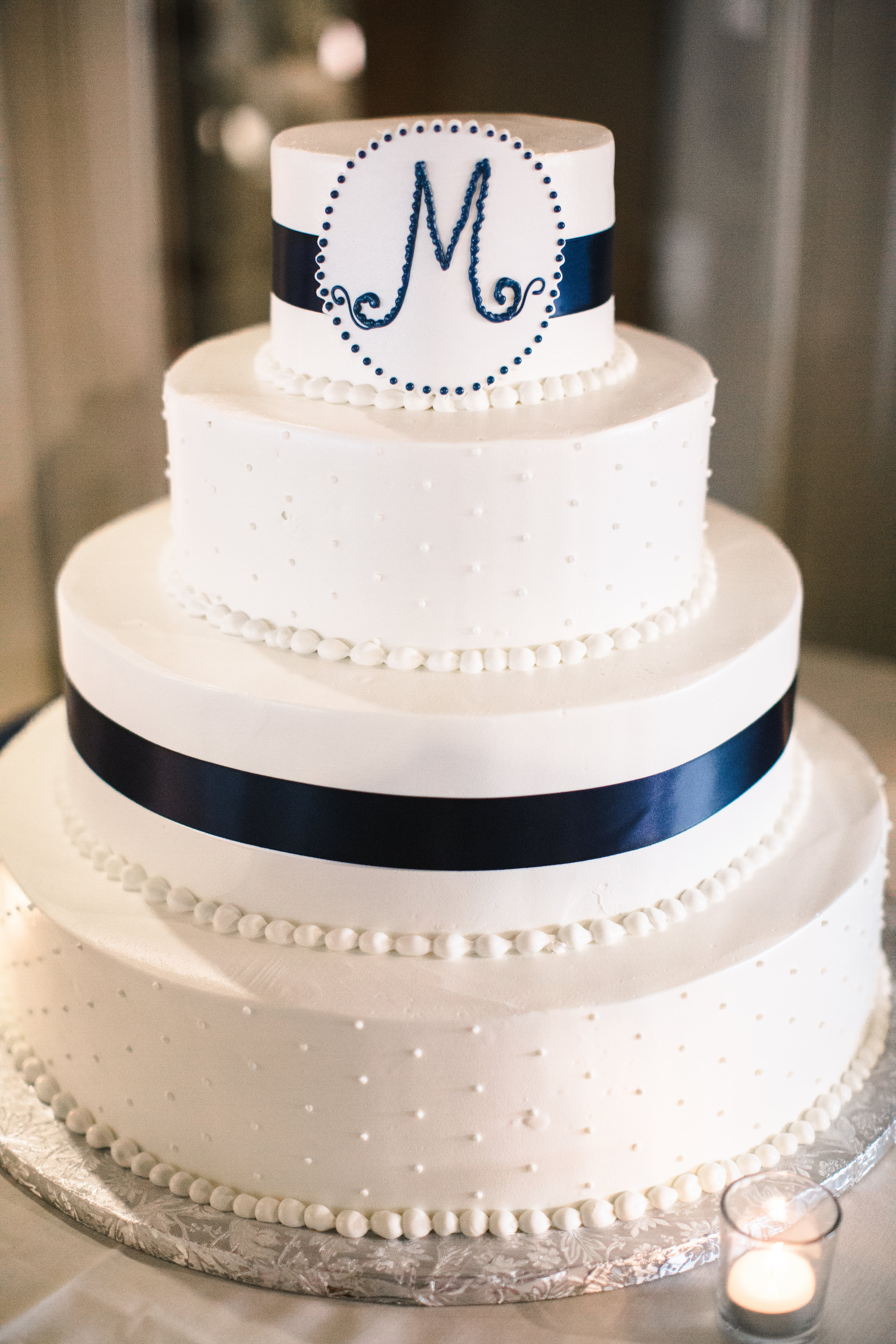 A white fourtier wedding cake decorated with polka dot